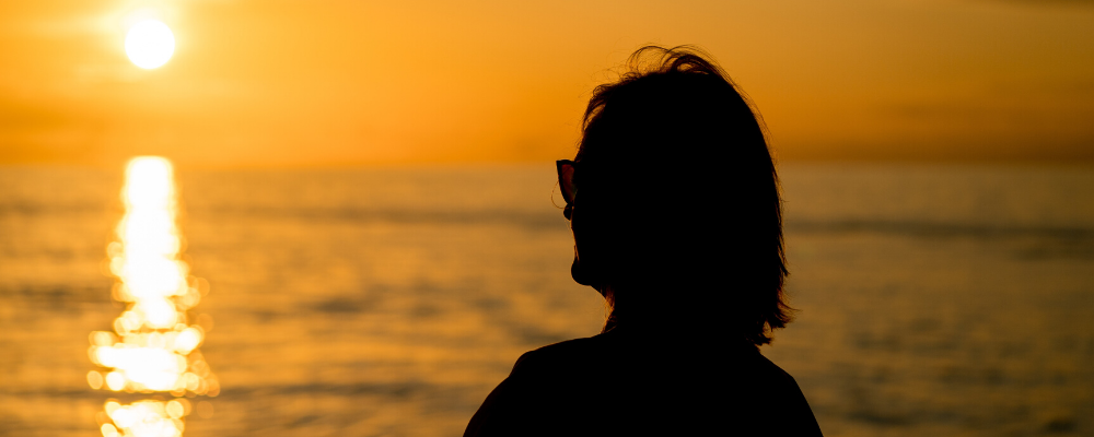 silhouette of woman looking at sunset over water